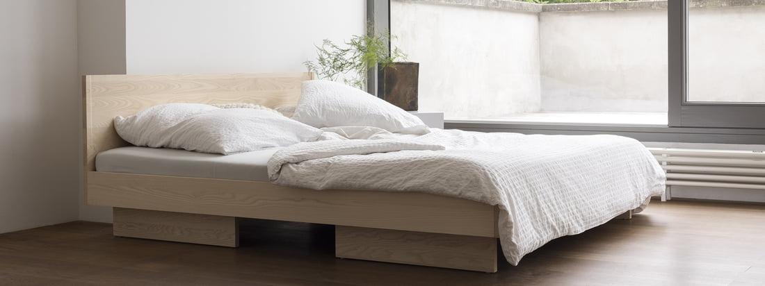 Le lit de Zian avec sa tête de lit par Objekte unserer Tage dans la vue d'ambiance. Des formes simples et des lignes droites caractérisent le design calme et non agité du lit, qui s'intègre parfaitement à toute chambre à coucher grâce à son aspect réduit.