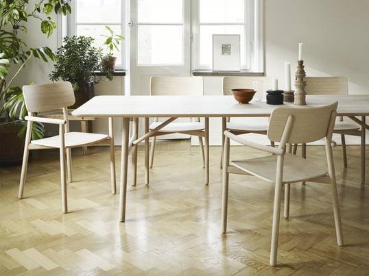 La table Hven 94x260cm avec la chaise à accoudoirs de Skagerak dans une illustration en environnement. La collection a été imaginée par le designer suédois Anton Björsing.