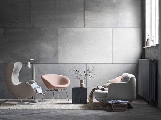 Le confortable canapé 2 places Lune de Fritz Hansen avec le fauteuil pot assorti dans des tons doux de gris et de rose. Une ambiance de salon moderne devant un mur gris.