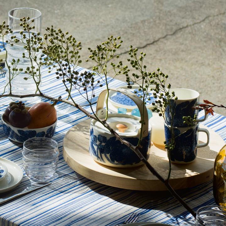 Le mug à anse et la théière Oiva Mynsteri de Marimekko en bleu / blanc présentés sur une table dressée